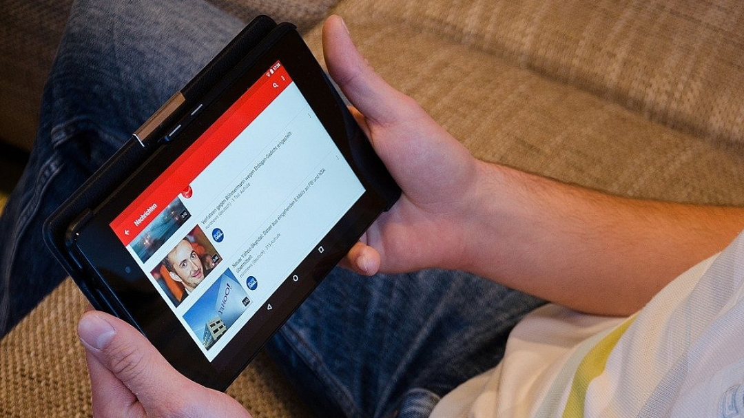 person holding a tablet showing list of YouTube videos